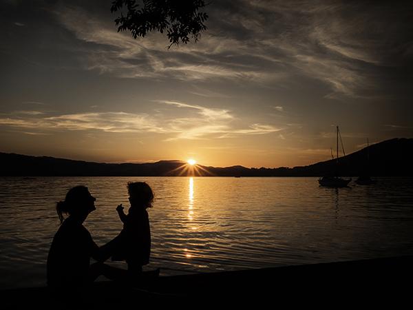 Foto: Wilhelm Watschka Fotografie. Mutter und Kind vor einem See als Silhouette. Hinter den Bergen geht gerade die Sonne unter. Aufgenommen am Attersee - Oberösterreich