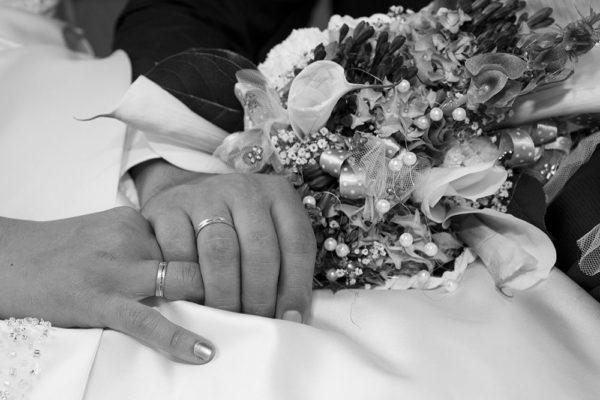 Ein Mann hält zärtlich nach der Hochzeit die Hand seiner Braut. Man sieht die Ringe und den Blumenstrauß. Foto wurde gemacht von Wilhelm Watschka