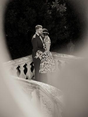 Ein Brautpaar steht bei einem Geländer aus Stein und hält sich romantisch im Arm. Das Fotos wurde von Wilhelm Watschka gemacht