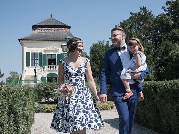 Foto: Wilhelm Watschka Fotografie. Nach der Hochzeit spaziert ein Paar mit ihrer Tochter im Arm den Park entlang