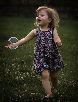 Ein kleines Kind jagt einer Seifenblase hinterher. Es läuft über eine Blumenwiese. Foto wurde von Wilhelm Watschka gemacht