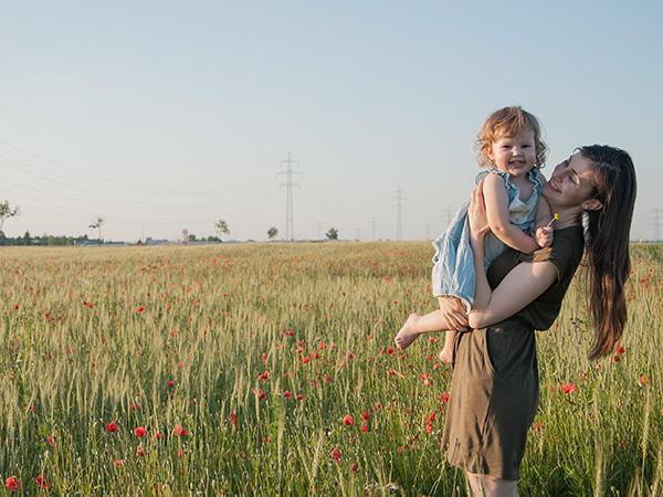 Foto: Wilhelm Watschka Fotografie. Dieses Bild zeigt, wie eine Mutter ein Kind im Arm hält und in einem Blumenfeld steht und beide lächeln