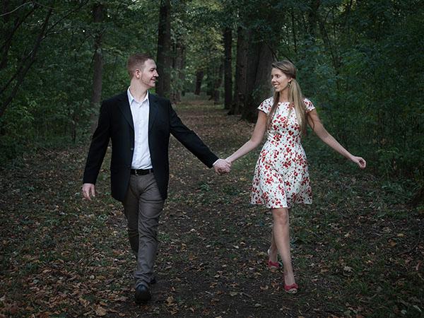 Foto: Wilhelm Watschka Fotografie. Ein verliebtes Paar spaziert Händchenhaltend durch einen Laubwald und strahlt sich dabei an.