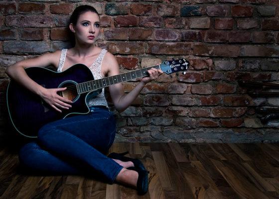 Foto: Wilhelm Watschka Fotografie I Eine Frau sitzt in einem Raum am Boden und spielt Gitarre.
