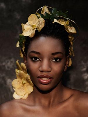 Foto: Wilhelm Watschka Fotografie I Portrait einer Frau mit gelben Blumen in den Haaren.