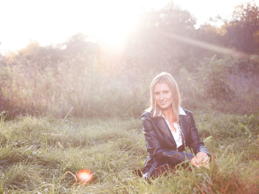 Foto: Wilhelm Watschka Fotografie I Eine Frau sitzt in einer Wiese und hinter ihr geht die Sonne unter. Im Bild sind Blendflecken zu sehen. Traumhaft schön!