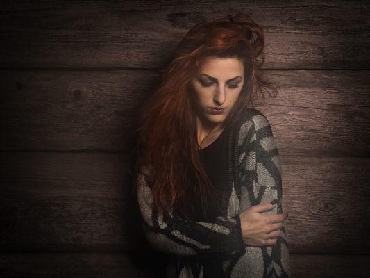 Fotograf: Wilhelm Watschka Fotografie I Eine Frau steht bei einer Wand und sieht zu Boden.