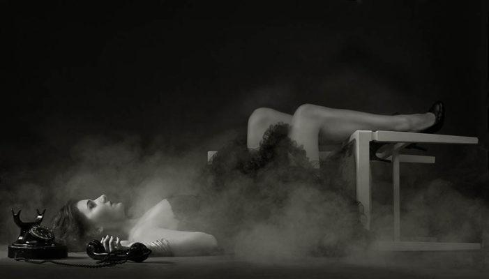 Foto: Wilhelm Watschka Fotografie Dieses Bild zeigt eine Frau, die am Boden liegt mit einem Sessel, vor ihr ein Telefon und sie wird von leichtem Nebel umhüllt. Diese Aufnahme erinnert an alte s/w Filme.