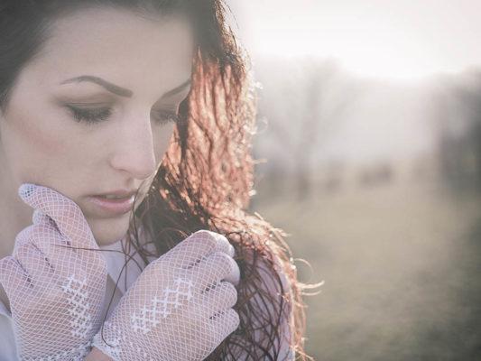 Portrait-Foto einer Frau im Freien. Die Frau sieht Richtung Boden. Dadurch wirkt das Bild sehr zärtlich, einfühlsam und romantisch. Im Hintergrund sind eine Wiese und Bäume zu sehen. Foto wurde gemacht von Wilhelm Watschka