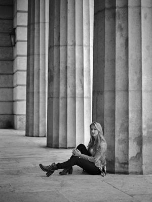 Fotograf: Wilhelm Watschka Fotografie I Eine Frau sitzt bei Säulen auf dem Boden und winkelt ein Bein an.