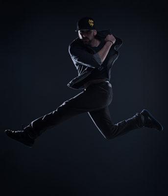 Ein Mann springt im Studio. Seine Beine sind gespreizt und sein Körper ist unter Anspannung. Foto wurde gemacht von Wilhelm Watschka.